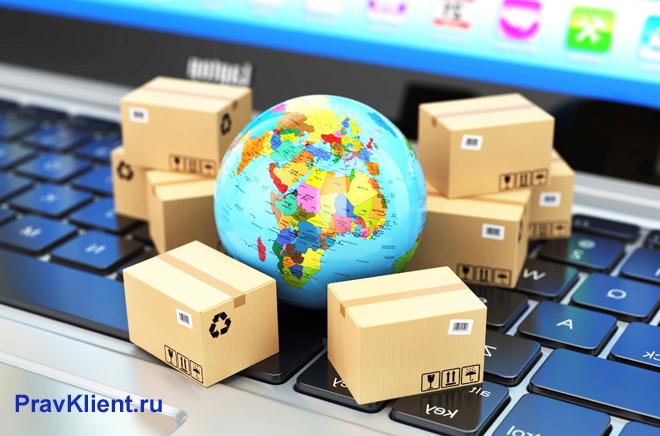 На клавиатуре ноутбука лежат маленький глобус и коробки