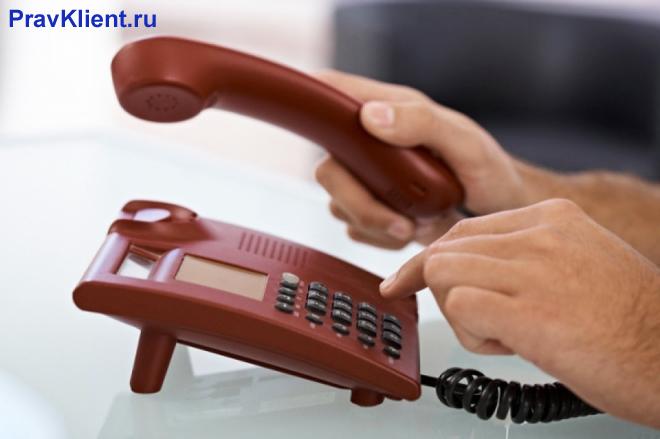 Мужчина делает звонок по стационарному телефону