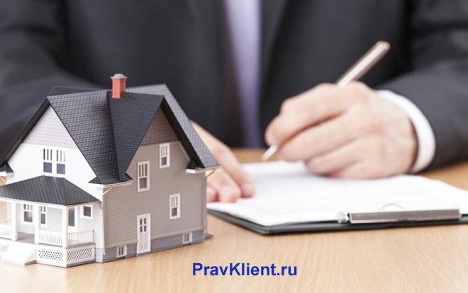 Бизнесмен пишет в тетради за столом, рядом стоит серый домик