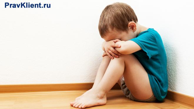 Обиженный мальчик сидит на полу