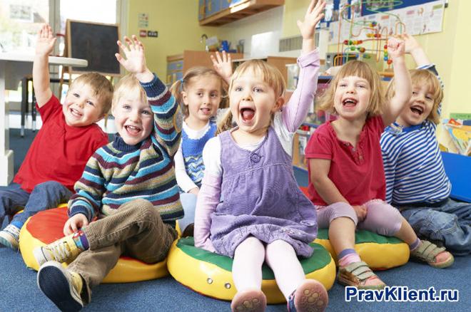 Дети в детском саду тянут руку вверх