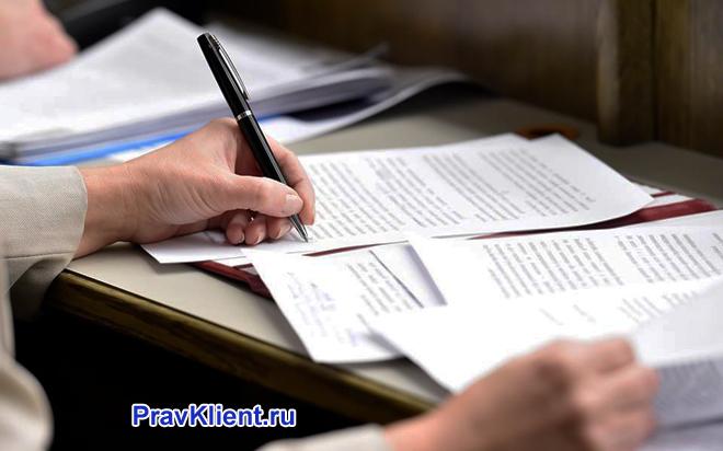 Мужчина заполняет бумаги, сидя за столом