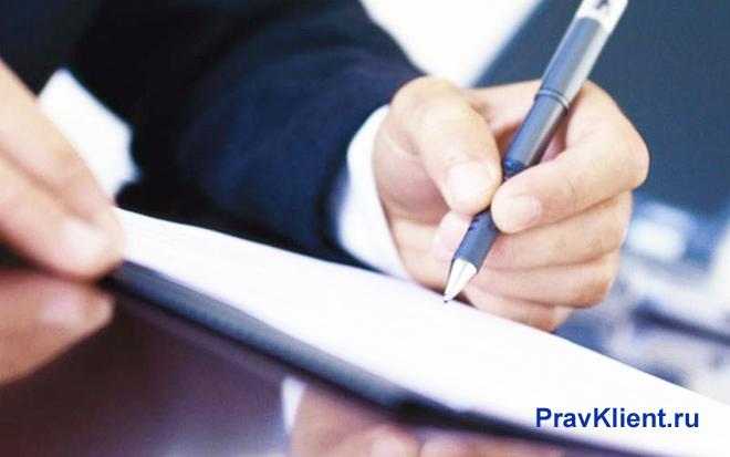 Бизнесмен пишет ручкой на листке бумаги