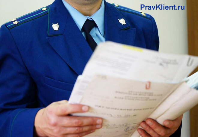Сотрудник прокуратуры читает документы