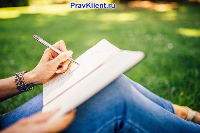Девушка сидит на лужайке и пишет на листке