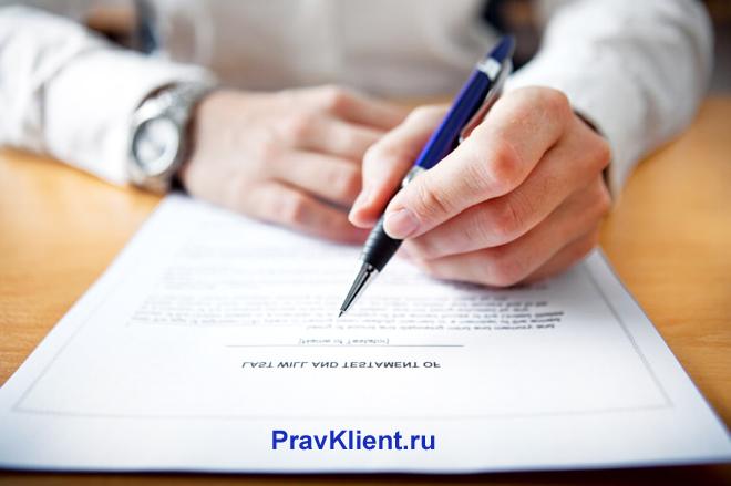 Молодой человек подписывает синей ручкой документы