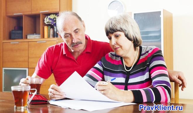 Семейная пара сидя за столом изучает документацию