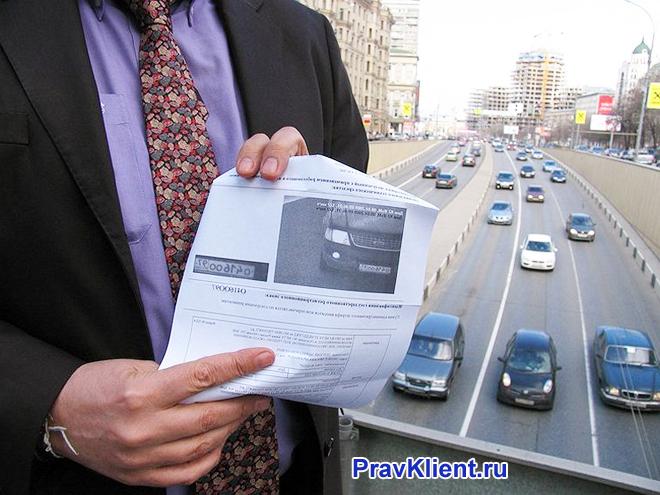 Бизнесмен держит в руке распечатку о нарушении ПДД