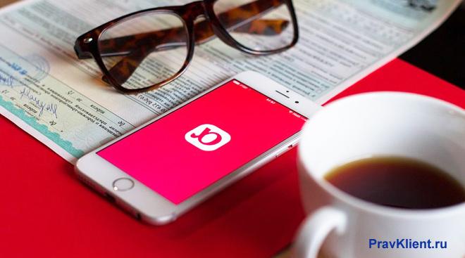 Приложение Альфа-Страхование в телефоне, очки, чашка с чаем, документ