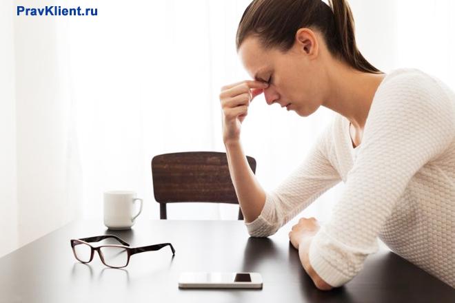 Расстроенная девушка сидит за письменным столом