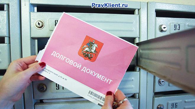 Девушка достает из почтового ящика долговой документ