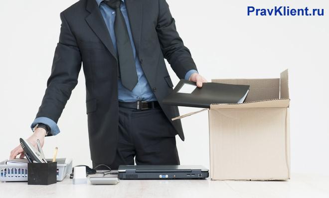 Сотрудник фирмы собирает свои личные вещи в картонную коробку