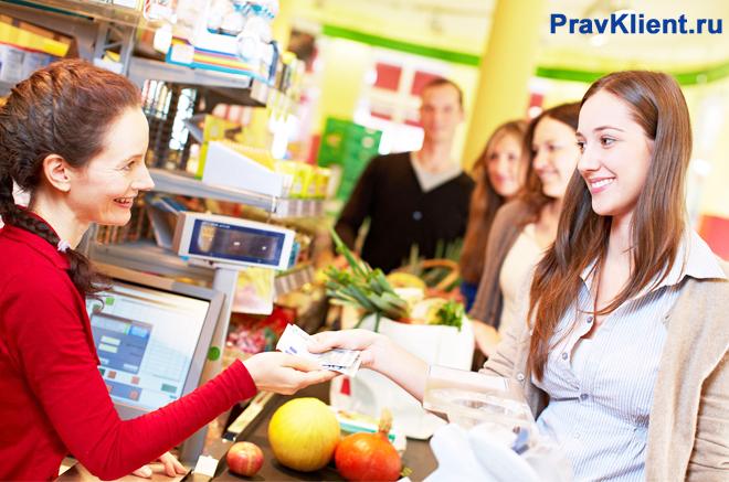 Покупатели проносят покупки через кассу