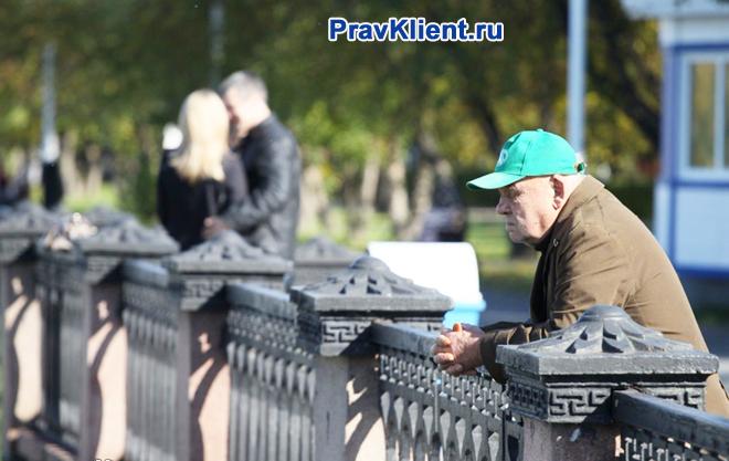 Одинокий пенсионер стоит на мосту