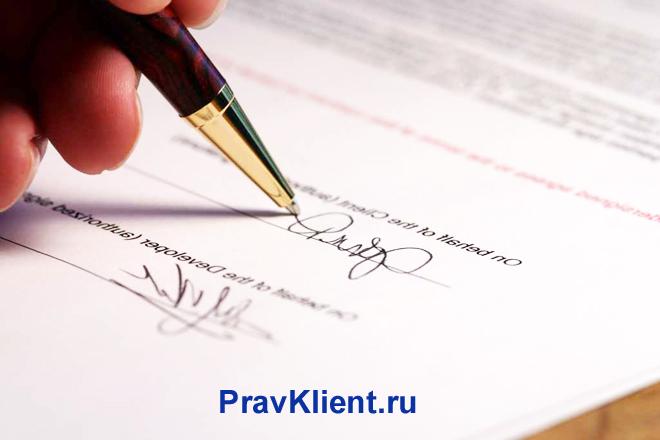 Человек ставит свою подпись на документе