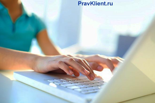 Девушка печатает на клавиатуре ноутбука