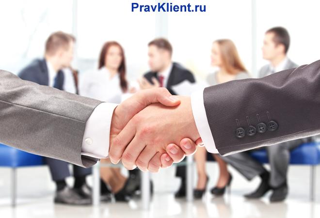 Рукопожатие бизнес-партнеров на фоне офисных работников