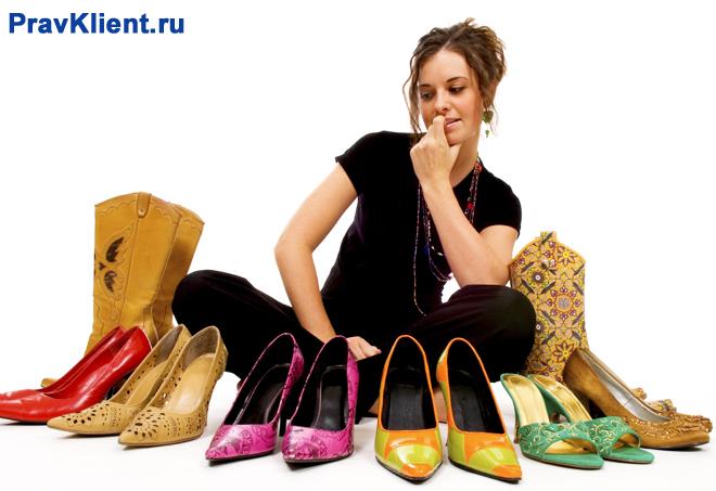 Девушка выбирает пару обуви, чтобы надеть