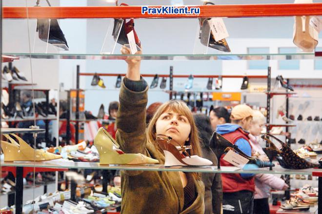 Девушка выбирает туфли в обувном магазине