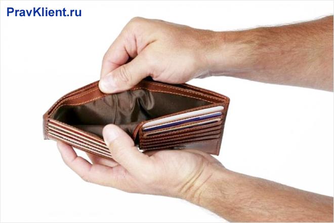 Мужчина держит в руке пустой кошелек