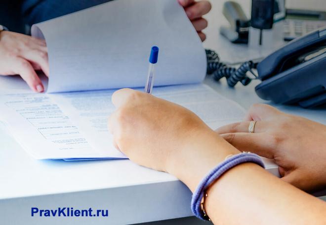 Девушка расписывается в документах в офисе