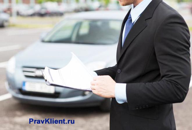 Мужчина читает документы на фоне автомобиля