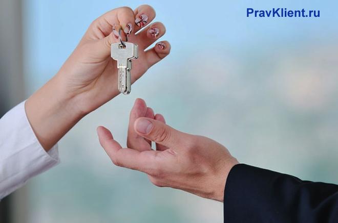 Девушка передает ключи мужчине в руки