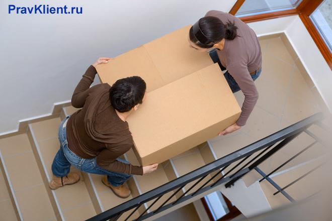 Мужчина и женщина несут большую картонную коробку по лестнице