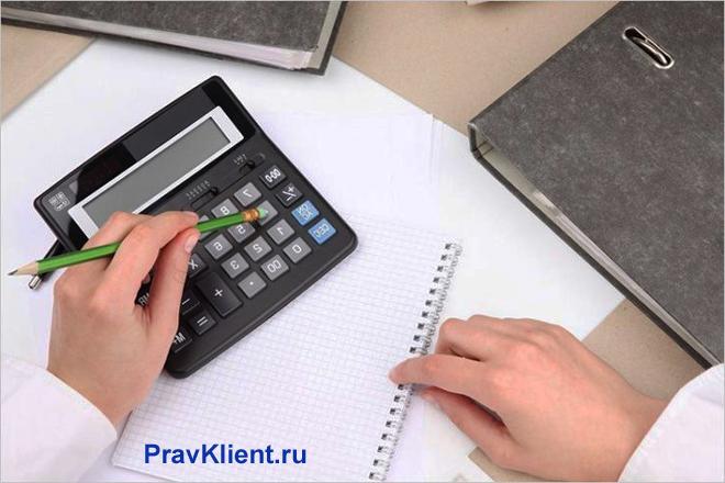 Мужчина считает на калькуляторе, на столе лежат тетрадь и папки
