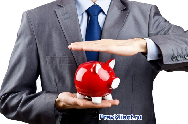 Бизнесмен держит в руке красную копилку