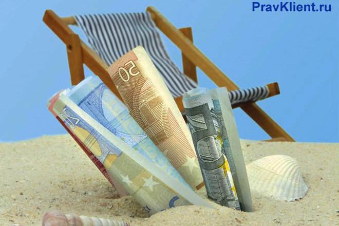 Деньги в песке, на заднем фоне шизлонг