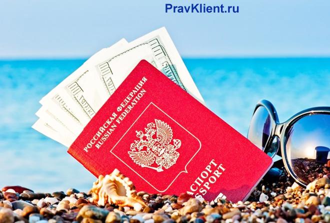 Паспорт с деньгами внутри, очки лежат на берегу моря