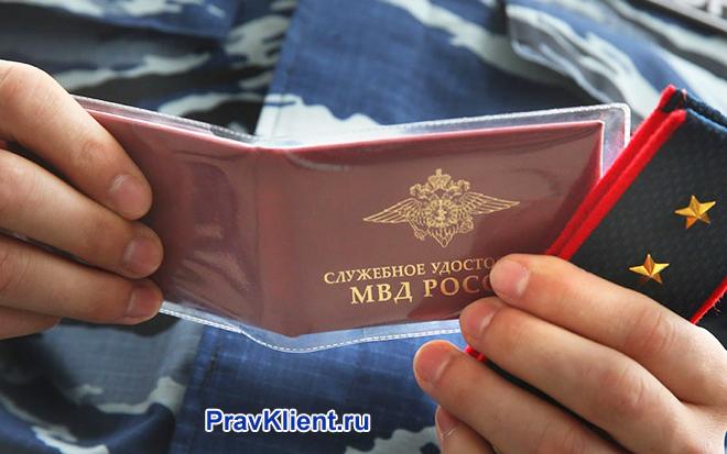 Военный держит в руке служебное удостоверение