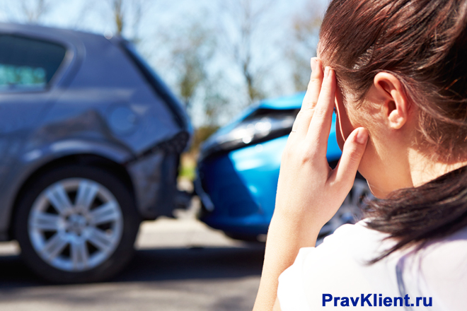 Девушка смотрит на разбитый автомобиль