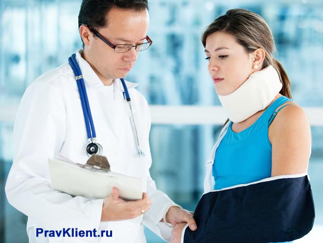 Девушка со сломанной рукой общается с врачом