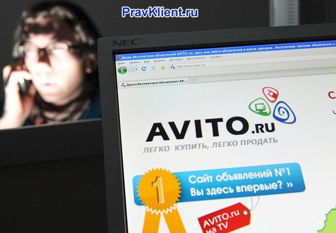 Сайт Авито на экране компьютера, на заднем фоне женщина звонит по телефону