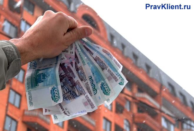 Мужчина держит в руке деньги за квартиру