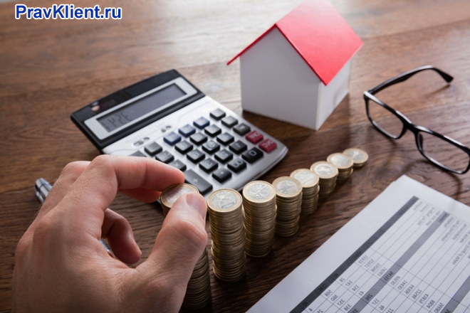 Мужчина пересчитывает деньги за дом на калькуляторе