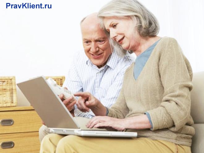 Семейная пара в возрасте пользуется ноутбуком