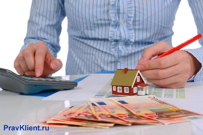 Мужчина в голубой рубашке считает стоимость недвижимости