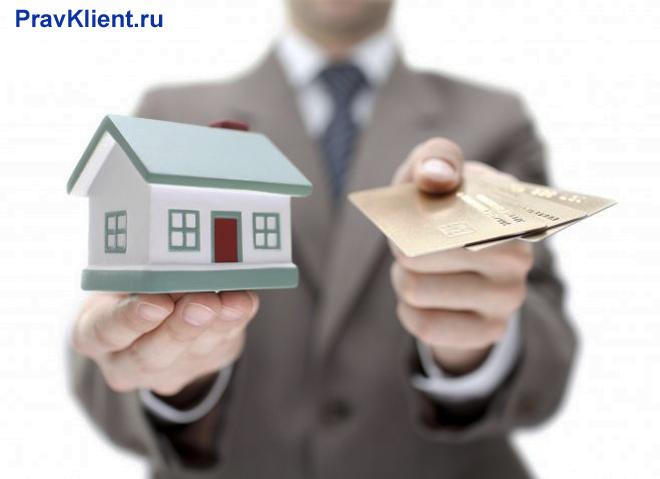 Бизнесмен держит в руках зеленый домик и банковские карточки