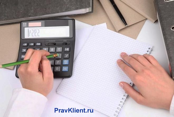 Мужчина считает на калькуляторе, на столе лежат бумаги, тетрадь