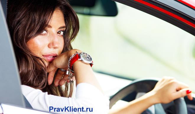 Молодая женщина за рулем красного автомобиля