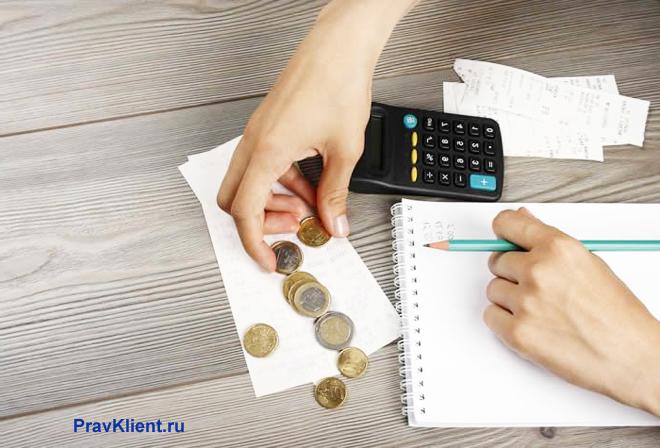 Девушка пересчитывает монетки за столом