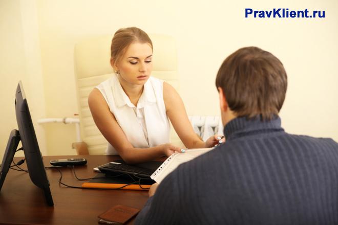 Сотрудница принимет документы у клиента фирмы