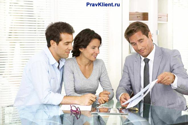 Консультант показывает документы семейной паре