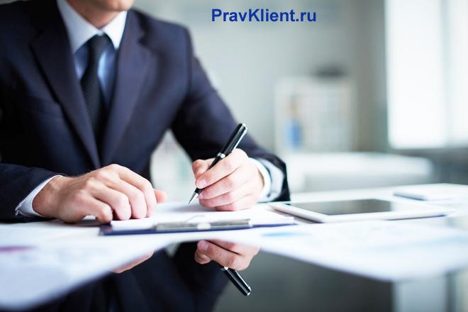 Бизнесмен за своим рабочим местом рассматривает документы