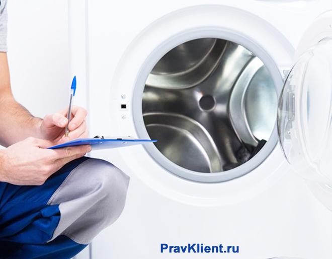 Рабочий осматривает стиральную машину
