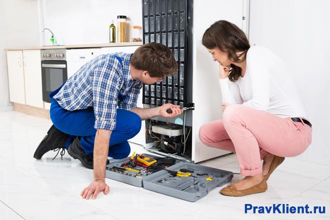 Работник ремонтирует холодильник