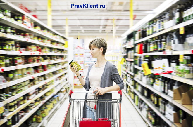 Девушка покупает продукты в супермаркете